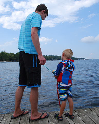 teaching a kid to fish with a push buttom reel